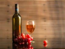 Bottiglia e vetro con vino sulla terra della parte posteriore di legno Fotografie Stock Libere da Diritti