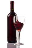 Bottiglia e vetro del vino rosso con spruzzata su fondo bianco Fotografia Stock