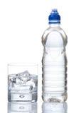 Bottiglia e vetro di acqua minerale con le goccioline fotografia stock libera da diritti