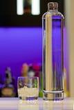 Bottiglia e vetro trasparenti della vodka alla barra Fotografia Stock Libera da Diritti