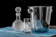 Bottiglia e vetro vuoti del cubetto di ghiaccio sul backgrou di legno blu della tavola Immagini Stock Libere da Diritti