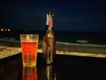 Bottiglia ed erba di birra sulla tavola alla spiaggia durante la notte Fotografia Stock Libera da Diritti
