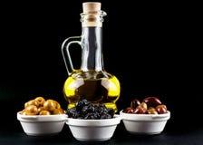 Bottiglia ed olive di olio d'oliva in ciotole sul nero Immagini Stock Libere da Diritti