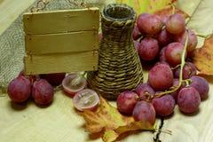 Bottiglia ed uva di vimini Fotografia Stock Libera da Diritti