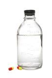 Bottiglia medica con salino e pillole al lato di esso Fotografia Stock