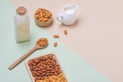 Bottiglia per il latte e del mandorla su fondo leggero Dadi della mandorla in spoo Fotografie Stock