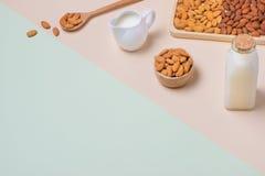 Bottiglia per il latte e del mandorla su fondo leggero Dadi della mandorla in spoo Fotografia Stock Libera da Diritti
