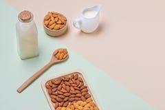 Bottiglia per il latte e del mandorla su fondo leggero Dadi della mandorla in spoo Fotografie Stock Libere da Diritti