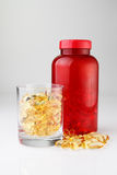 Bottiglia rossa con le capsule dell'olio in tazza di vetro Fotografia Stock Libera da Diritti