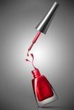 Bottiglia rossa dello smalto di chiodo con spruzzata Immagini Stock