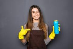 Bottiglia sorridente della tenuta della donna di chimica per fare piazza pulita ed indicata sopra isolato su grey immagini stock