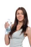 Bottiglia sottile della holding della donna di acqua potabile tranquilla Fotografie Stock Libere da Diritti