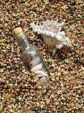 Bottiglia sulla priorità bassa della mare-spiaggia Fotografie Stock Libere da Diritti