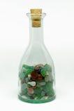 Bottiglia trasparente con le pietre variopinte Fotografia Stock Libera da Diritti