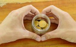 Bottiglia umana della tenuta della mano della moneta di oro con forma del cuore Fotografia Stock