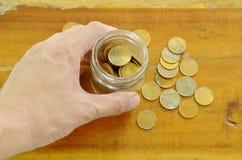 bottiglia umana della tenuta della mano della moneta di oro sulla tavola Fotografia Stock