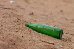 Bottiglia verde sulla sabbia della spiaggia - bevanda di celebrazione del partito - bottiglia abbandonata Immagini Stock