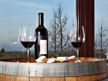 Bottiglia, vetri di vino con vino rosso ed aperitivo del formaggio sulla sbarra Fotografia Stock
