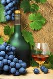 Bottiglia, vetro del cognac e mazzo di uva fotografie stock libere da diritti