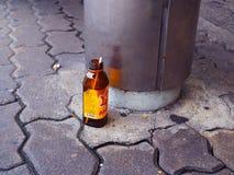 Bottiglia vuota della bevanda di sport M150 sul pavimento del sentiero per pedoni, alla fermata dell'autobus Fotografia Stock Libera da Diritti