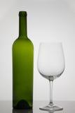 Bottiglia vuota di vino con bicchiere di vino vuoto su fondo bianco Fotografie Stock