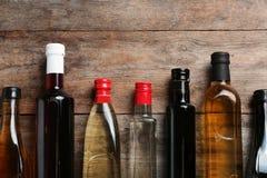 Bottiglie con differenti generi di aceto e di spazio per testo su fondo di legno immagini stock libere da diritti