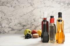 Bottiglie con differenti generi di aceto sulla tavola fotografie stock