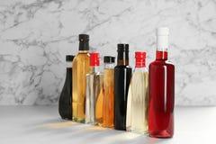 Bottiglie con differenti generi di aceto sulla tavola immagini stock
