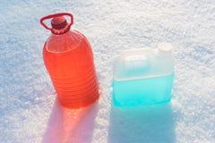 Bottiglie con il liquido di congelamento della rondella del parabrezza, fondo della neve Immagini Stock Libere da Diritti