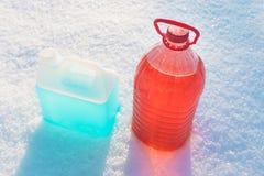 Bottiglie con il liquido di congelamento della rondella del parabrezza, fondo della neve Fotografia Stock