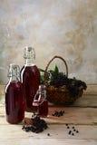 Bottiglie con il succo rosso dalle bacche di sambuco nere & da x28; Nig del Sambucus Fotografie Stock