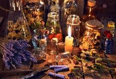 Bottiglie con le erbe, i fiori della lavanda, i rotoli di carta e gli oggetti magici sulla tavola della strega fotografia stock