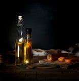 Bottiglie con petrolio, le erbe e le spezie alla tavola di legno su fondo nero Fotografie Stock