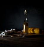 Bottiglie con petrolio, le erbe e le spezie alla tavola di legno su fondo nero Immagine Stock Libera da Diritti