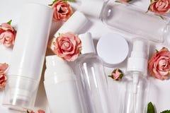 Bottiglie cosmetiche Benessere e raccolta di bottiglie della stazione termale con i fiori del parfume della molla Trattamento di  Immagini Stock Libere da Diritti