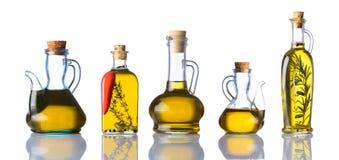 Bottiglie degli oli da cucina su fondo bianco Fotografia Stock