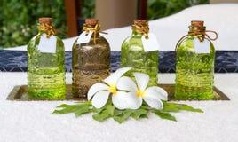 Bottiglie degli oli essenziali disposti sul leelawade della decorazione del letto Fotografie Stock