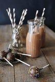 Bottiglie degli schiocchi del dolce e del latte sul piatto Fotografia Stock