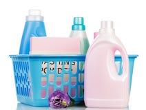 Bottiglie del canestro e della plastica di lavanderia con il detersivo su bianco Fotografia Stock