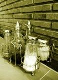 Bottiglie del condimento sul ripiano del tavolo del caffè Immagini Stock
