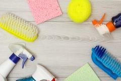 Bottiglie del detersivo, dei tovaglioli del microfiber di colore e delle spazzole sintetiche per pulire fotografia stock libera da diritti