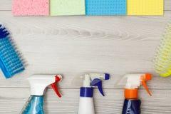 Bottiglie del detersivo, dei tovaglioli del microfiber di colore e delle spazzole sintetiche per pulire fotografia stock