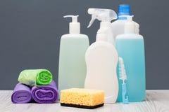 Bottiglie del detersivo, delle borse di immondizia e della spugna su fondo grigio immagini stock