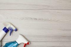 Bottiglie del detersivo per la pulizia sul fondo di legno grigio fotografia stock