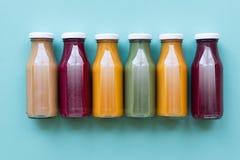 Bottiglie del succo di verdura e della frutta isolate su fondo blu Stile naturale dell'alimento biologico fotografie stock libere da diritti