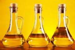 Bottiglie dell'olio di oliva su priorità bassa gialla Immagine Stock Libera da Diritti