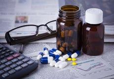 Bottiglie della medicina, pillole e dati finanziari Fotografie Stock Libere da Diritti