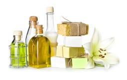 Bottiglie della stazione termale, pezzi del sapone e giglio isolati su bianco Immagini Stock