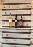 Bottiglie delle bevande alcoliche su uno scaffale di legno Immagini Stock Libere da Diritti