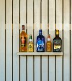 Bottiglie delle bevande alcoliche su uno scaffale di legno Fotografie Stock Libere da Diritti